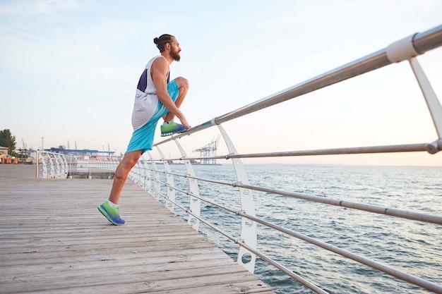 Ritratto di giovane ragazzo barbuto attraente che fa stretching per le gambe, esercizi mattutini in riva al mare, riscaldamento dopo la corsa.