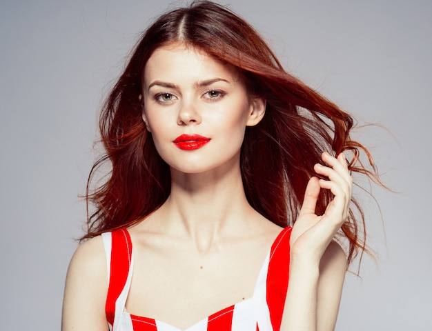 Portrait of a young attractive and beautiful woman with red lips, red flying hair
