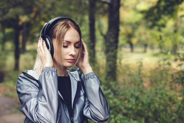 Portrait of young attractive blonde girl on a city park,  listening to music on headphones