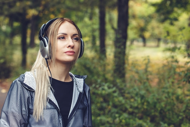 Portrait of young attractive blonde woman on a city park, listening to music on headphones
