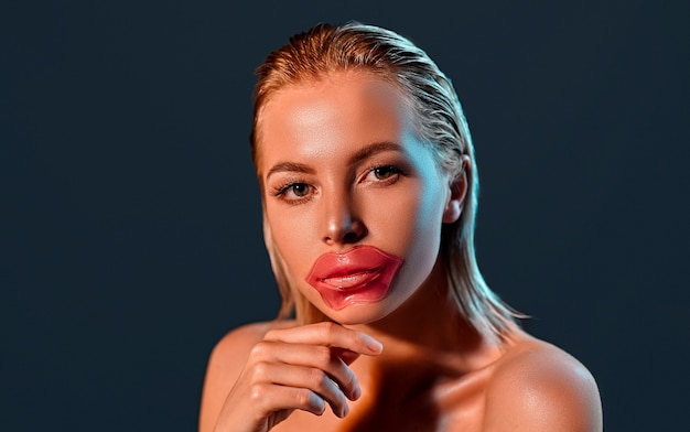 Portrait of a young attractive blonde woman with shining skin with a lip patch on black wall
