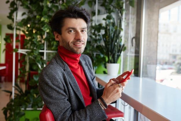 Ritratto di giovane uomo barbuto dai capelli castani attraente che tiene smartphone in mano alzata e guarda volentieri la fotocamera con un sorriso leggero, isolato sopra l'interno del caffè della città