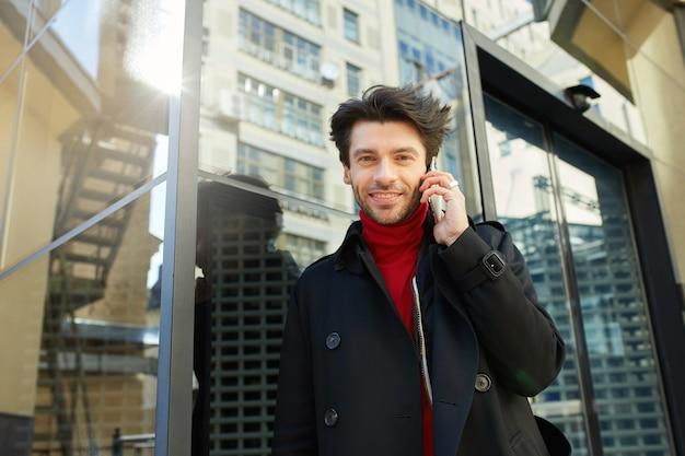 Ritratto di giovane maschio dai capelli castani attraente vestito in abiti formali guardando allegramente la fotocamera con un sorriso affascinante pur avendo piacevole conversazione telefonica