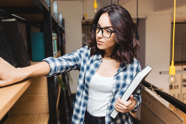 Portrait young attractive brunette woman in black glasses in library looking for books. smart student, studying time, good work, academic.