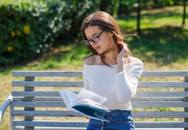 Portrait of young attractive brunette woman reading book, sitting at summer green park.