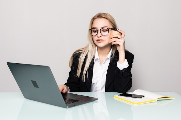 Portrait of a young and attractive business woman sitting at her office work desk having a telephone conversation and using a laptop computer, isolated on a white wall.