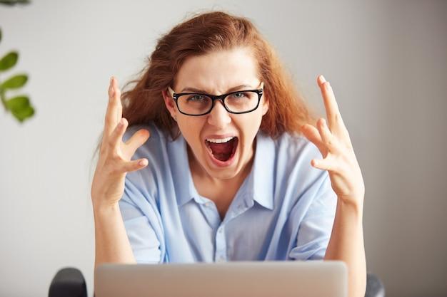 Ritratto di una giovane donna di affari attraente con sguardo frustrato che lavora al computer portatile