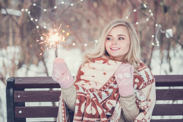 Portrait of young attractive celebrating woman holding sparkles.