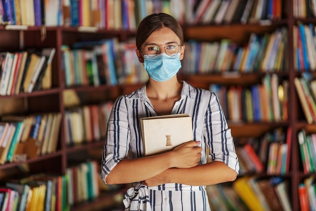 Portrait of young attractive college girl standing in library with face mask on, holding a book