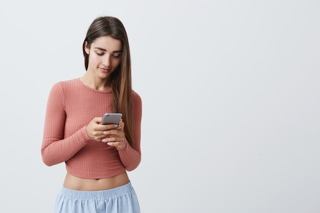 Portrait of young attractive dark-haired caucasian girl with long hair in pink crop top and blue jeans chatting with boyfriend about night date on her smartphone with happy expression.