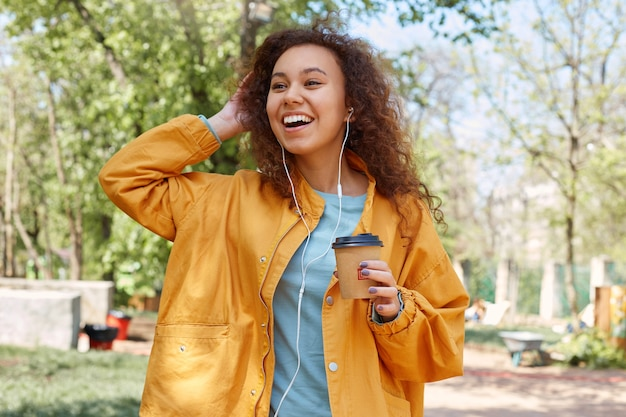 Portrait of young attractive dark skinned curly girl broadly smiling, walking in the park, goes to meet his friends listening music, holding a cup of coffee, wearing a yellow jacket.