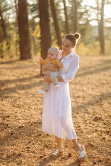 Portrait of young attractive family with little baby son, posing in beautiful autumn pine forest at sunny day. handsome man and  his pretty brunette wife