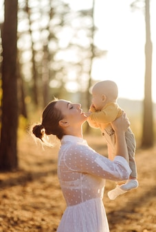 Ritratto di giovane famiglia attraente con figlio piccolo bambino, in posa nella bellissima pineta autunno al giorno pieno di sole. bell'uomo e la sua bella mora moglie