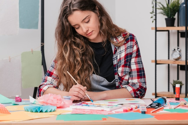 Portrait of a young attractive female artist painting on paper
