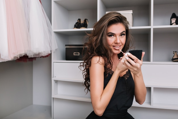 Portrait of a young attractive girl sitting in the dressing room and makes make-up, with lipstick in hand. she dressed in a stylish outfit surrounded by clothes.