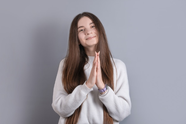 Portrait of a young attractive girl with dark long hair in which palms are folded together asking for something on a gray studio background. place for text.