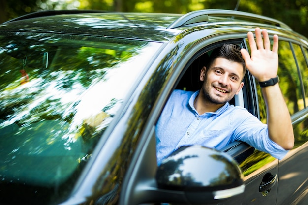 Portrait of young attractive handsome brunette man driving car and greeting somebody with hand