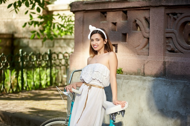Portrait of a young attractive happy woman smiling to the camera posing near her bicycle in the city center