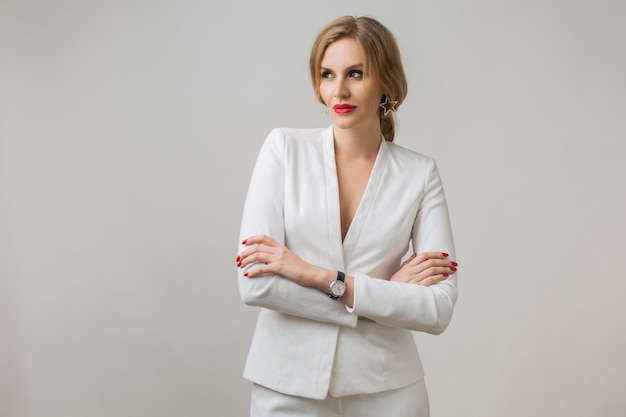 Ritratto di giovane donna attraente in abito bianco, donna d'affari sexy e sicura, indipendente, stile elegante, labbra rosse, espressione seria del viso, guardando a porte chiuse, braccia incrociate, sorriso