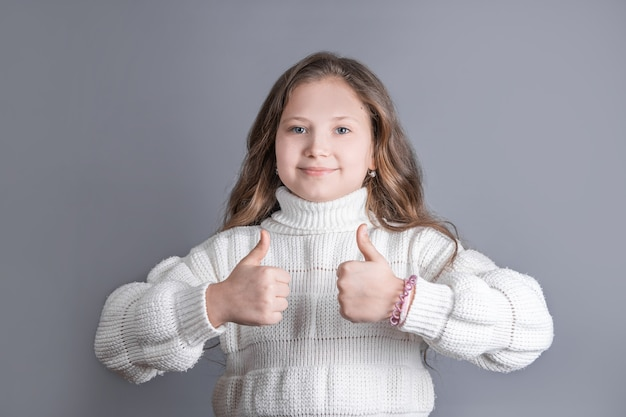 Portrait of a young attractive little girl with blond long flowing hair in a white sweater smiling shows thumbs up,like sing on a gray studio background. place for text. copy space.