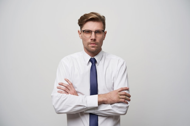Portrait of young attractive man looks evaluative