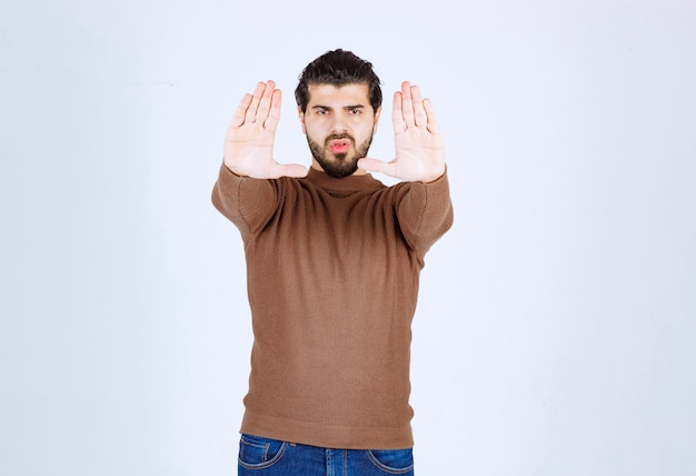 Portrait of a young attractive man making stop with his hands.