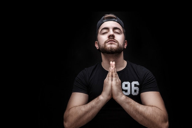 Portrait of young attractive man with dark hair wearing black shirt in yoga pose on black background