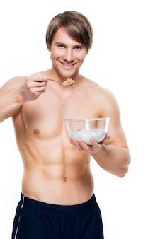 Ritratto di un giovane uomo muscolare attraente che mangia i fiocchi con latte - isolato sulla parete bianca.
