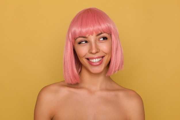 Portrait of young attractive pink haired female showing her perfect white teeth while smiling cheerfully, looking aside positively while standing over mustard wall