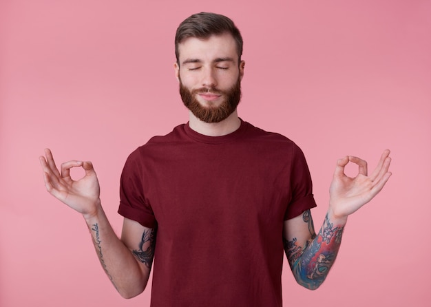 Portrait of young attractive red bearded man in blank t-shirt, looks peaceful and calm, smiles, stands over pink background with closed eyes and showing om gesture.