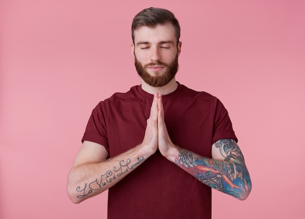 Portrait of young attractive red bearded man in blank t-shirt, looks peaceful and calm, smiles, stands over pink background with closed eyes and showing prayer gesture.