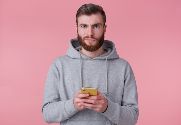 Portrait of young attractive red bearded man in gray hoodie, looks discontented,holding smartphone, looks at camera and stands over pink background.
