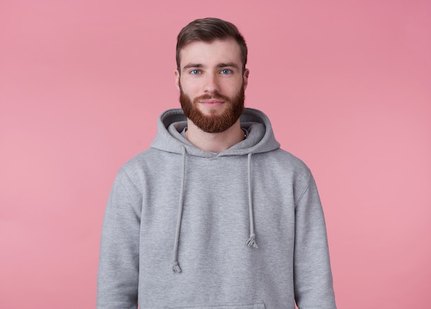 Portrait of young attractive red bearded man in gray hoodie, looks good and calm, smiles, stands over pink background.