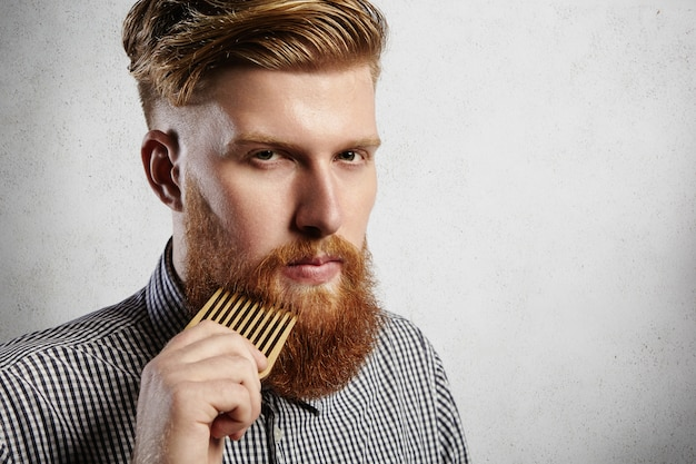 Portrait of young attractive redhead hipster male with serious and confident look, holding wooden comb and doing his thick beard. stylish bearded barber in checkered shirt combing in salon.