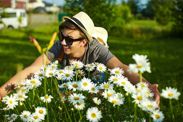 Portrait of young attractive smiling modern stylish man in casual cloth in hat in glasses in the park with bright colorful flowers in camomiles