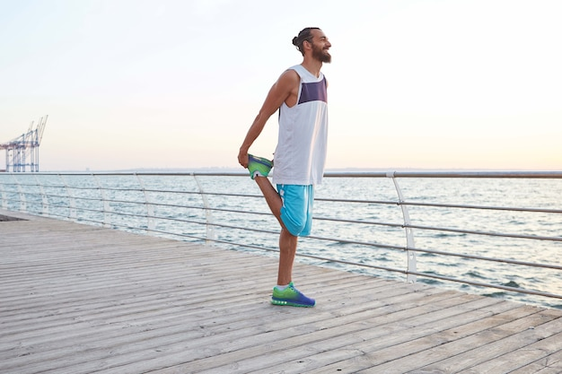Portrait of young attractive sporty bearded man doing stretching, morning exercises by the sea, warm-up after run, leads healthy active lifestyle. fitness male model.
