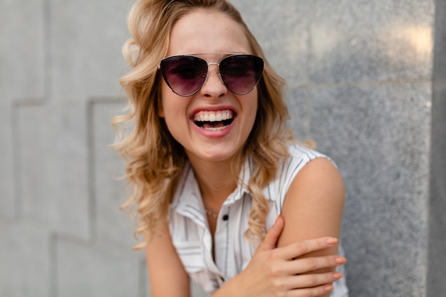 Portrait of young attractive stylish woman smiling  walking in city street in summer fashion style dress wearing sunglasses candid smile