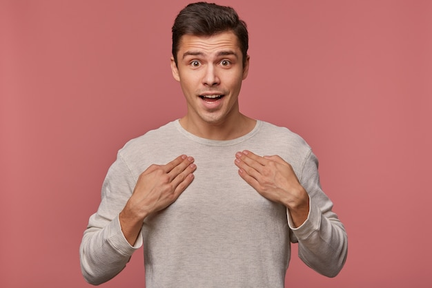 Ritratto di giovane uomo sorpreso attraente indossa in maglietta vuota, guarda la telecamera con felice espressione, punta a se stesso, isolato su sfondo rosa.