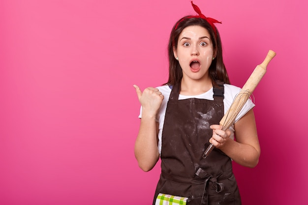 Portrait of young attractive woman in brown apron poses in studio, points thumb aside isolated on rose wall. astonished female stands with opened mouth, holds rolling pin. culinary concept.