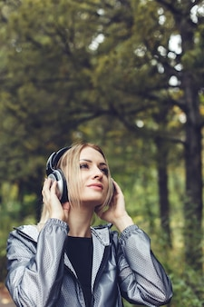 Portrait of young attractive  woman on a city park, listening to music on headphones