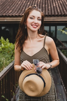 Portrait of young attractive woman in elegant dress, straw hat, summer style, fashion trend, vacation, smiling, stylish accessories, sunglasses, posing on tropical villa on bali