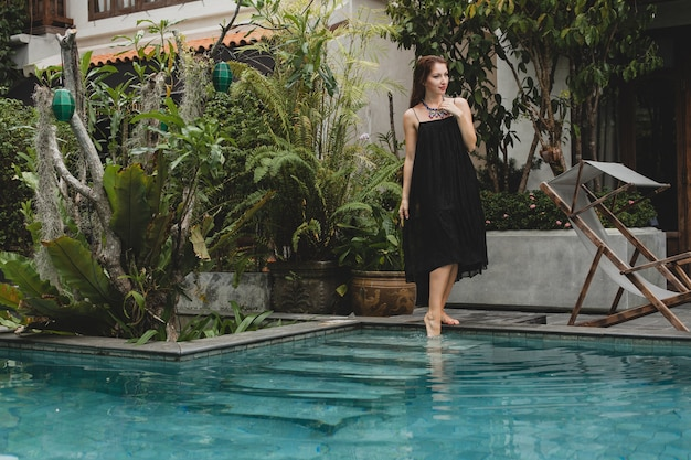 Ritratto di giovane donna attraente in abito elegante, cappello di paglia, stile estivo, tendenza moda, vacanze, sorridente, accessori alla moda, occhiali da sole, posa sulla villa tropicale a bali