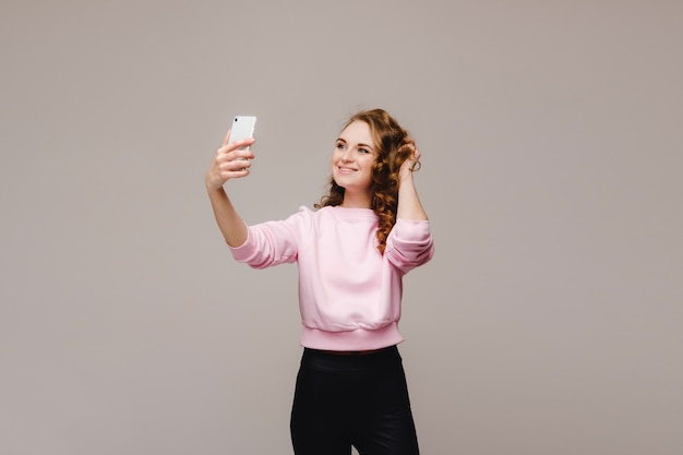 Portrait of a young attractive woman making selfie photo on smartphone isolated on a white background.