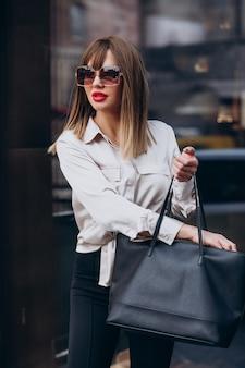 Ritratto di modello di giovane donna attraente che esamina la sua borsa