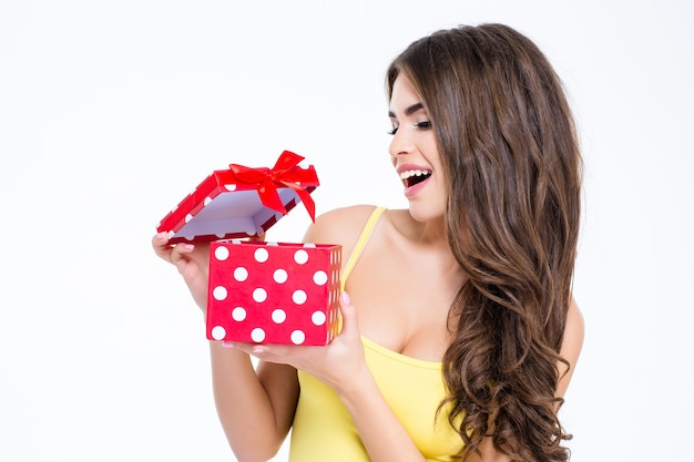 Portrait of a young attractive woman opening present box isolated on a white background