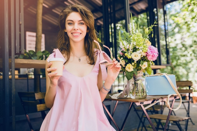 Portrait of young attractive woman sitting in cafe, summer fashion outfit, hipster style, pink cotton dress, sunglasses, smiling, drinking coffee, stylish accessories, trendy apparel, happy mood