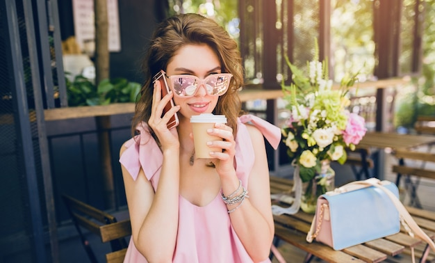 Portrait of young attractive woman sitting in cafe, summer fashion outfit, hipster style, pink cotton dress, sunglasses, smiling, drinking coffee, stylish accessories, trendy apparel, talking on phone