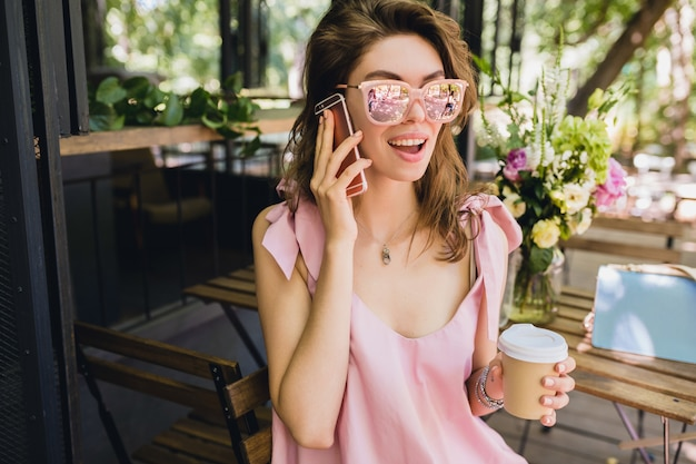 Portrait of young attractive woman sitting in cafe, summer fashion outfit, pink cotton dress, sunglasses, smiling, drinking coffee, stylish accessories, trendy apparel, talking on phone