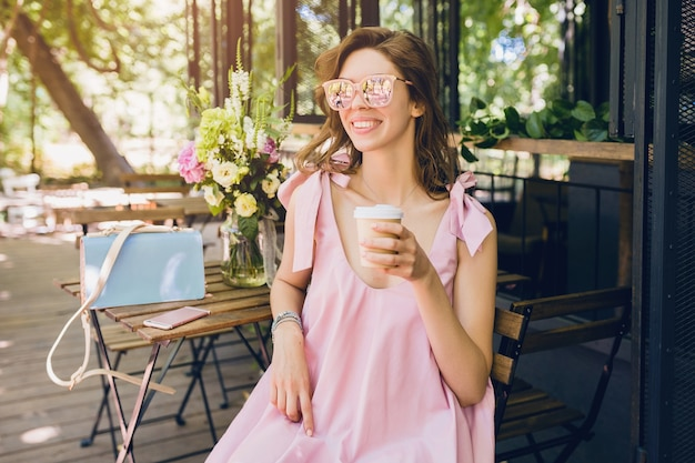 Portrait of young attractive woman sitting in cafe in summer fashion outfit