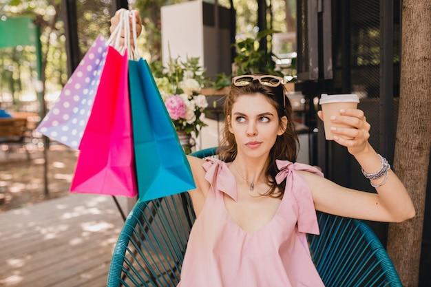 Ritratto di giovane donna attraente seduto in un caffè con le borse della spesa bere caffè, abito di moda estiva, abito di cotone rosa, abbigliamento alla moda, cercando perplesso, pensando